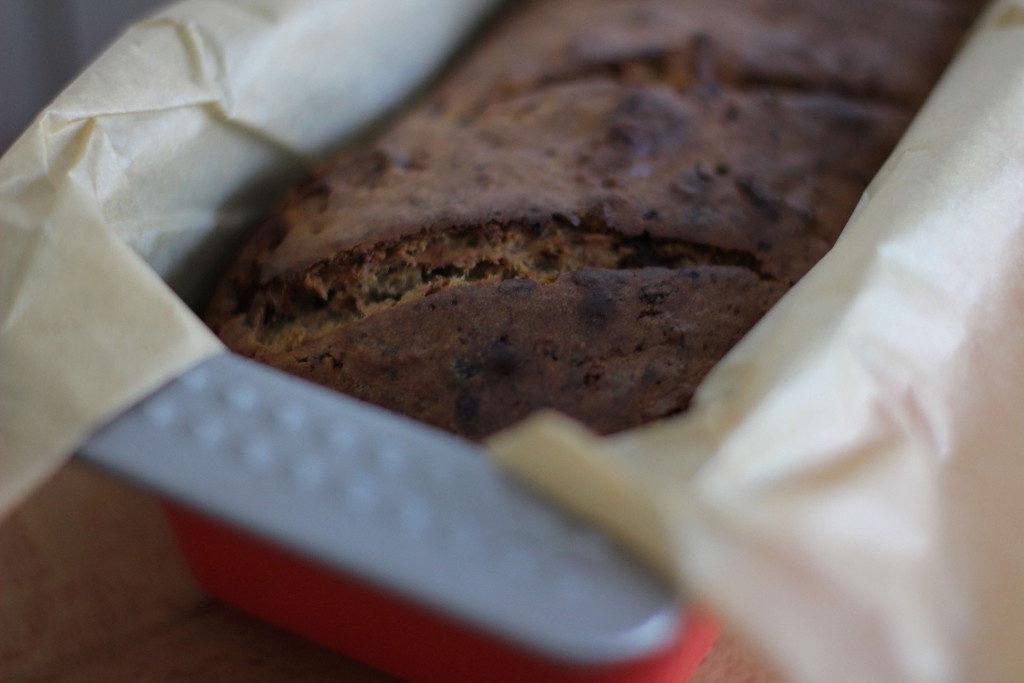 Bananenbrot mit Dinkelmehl & Zartbitterschokolade umwickelt von Backpapier in der Form